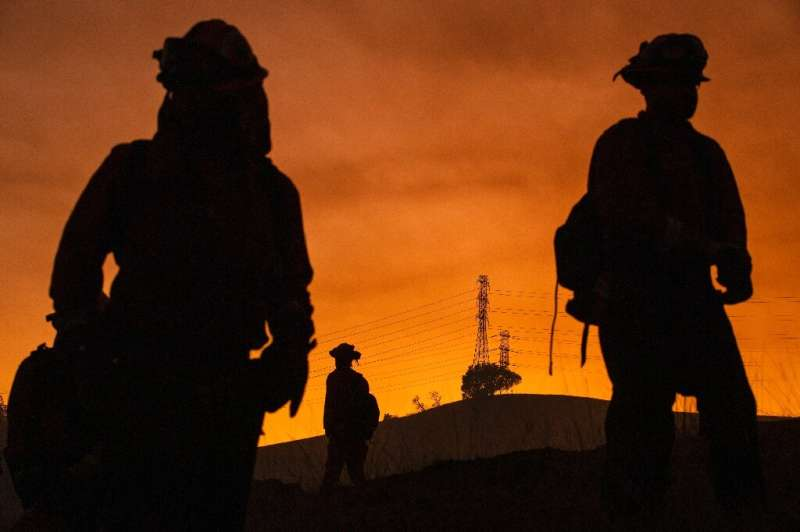 Members of an inmate firefighting crew are silhouetted against a hillside with a track of PG&E lines during firefighting ope