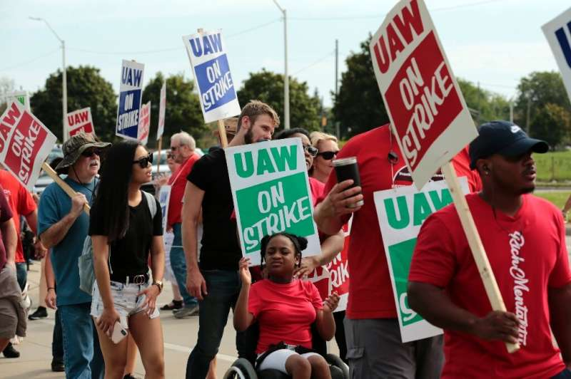 Moriha Ross, a member of the United Auto Workers, pushed her daughter Rhian on Sunday as they picketed outside of GM's Detroit-H