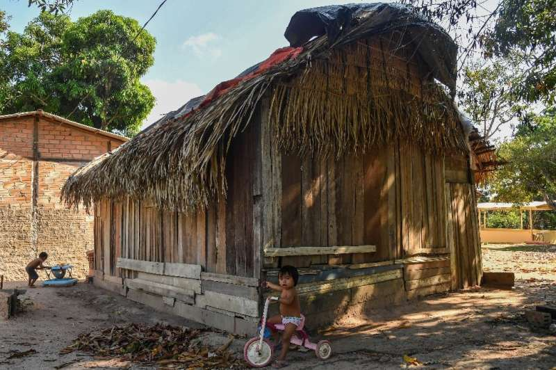Munduruku indigenous children play around a home in the Praia do Mangue indigenous reserve in Itaituba
