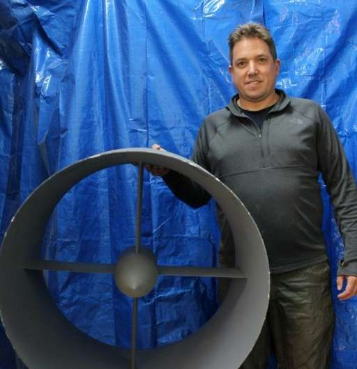 NFT co-founder Guy Kaplinsky poses with a model propeller before a curtain concealing work the startup is doing on a flying car