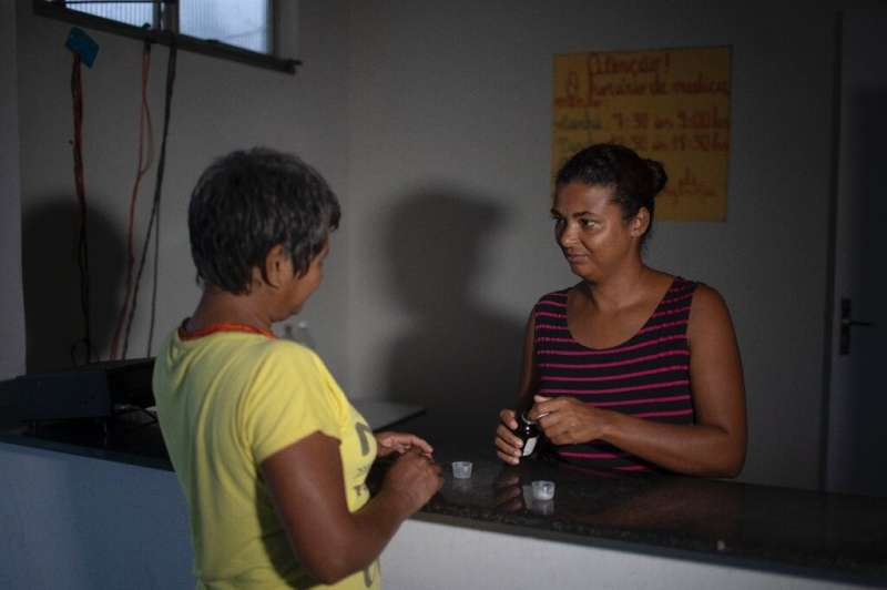 Nurse Karina Silva distributes medicine to an Arara indigenous woman in Laranjal—Marcal does two-month rotations in the village