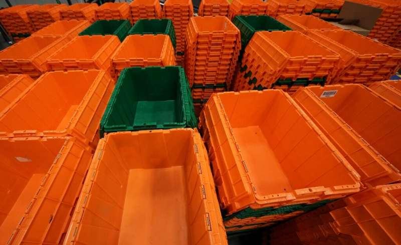 Orange and green plastic bins—the company's signature colors—zip along on conveyor belts overhead