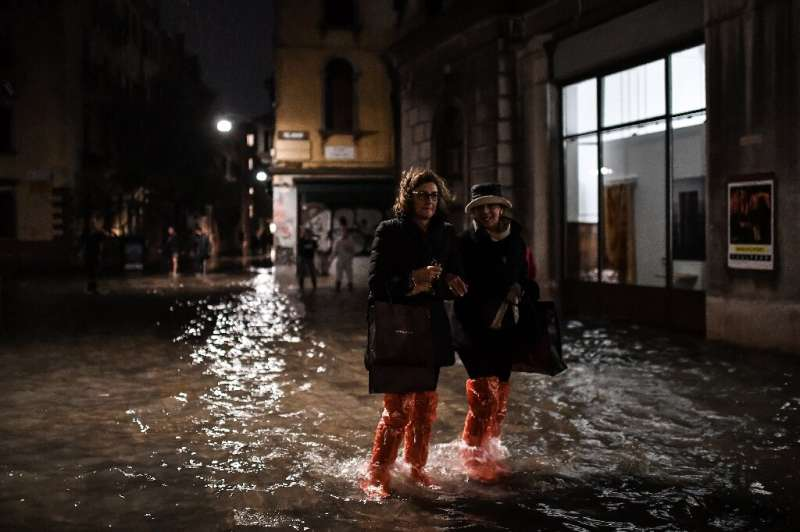"""People cross a flooded street during an exceptional """"acqua alta"""" on November 12 in Venice"""