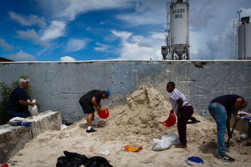 People fill sandbags donated by a ready-mix company to Miami-Dade residents preparing for Hurricane Dorian in West Miami