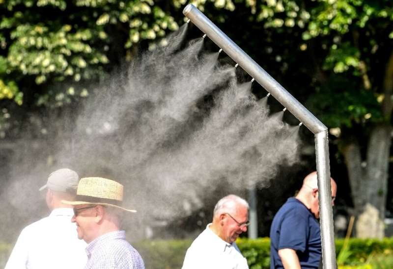 People refresh themselves under a mist sprayer in Lille, northern France