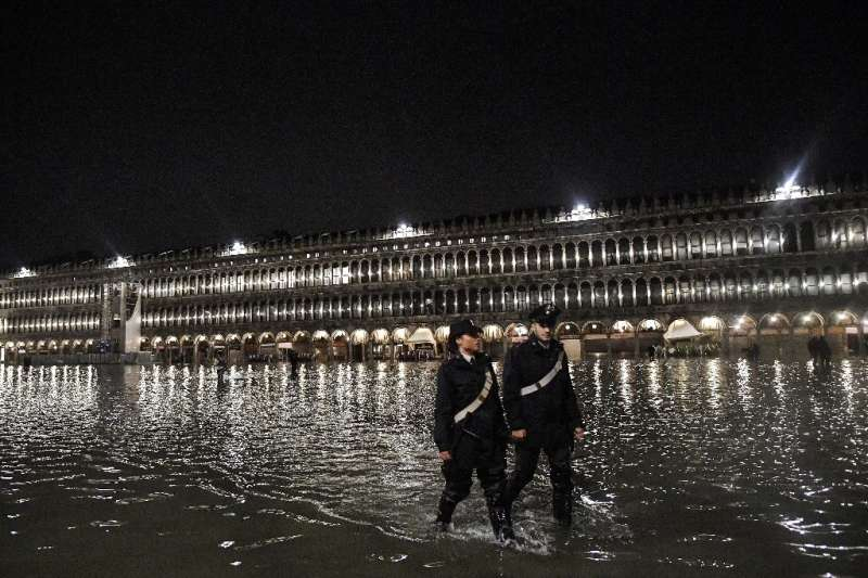 Police patrol flooded St. Mark's Square in Venice on November 12