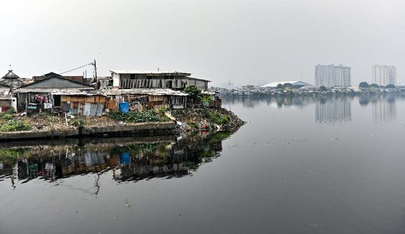 Public houses reach the edge of a reservoir in northern Jakarta