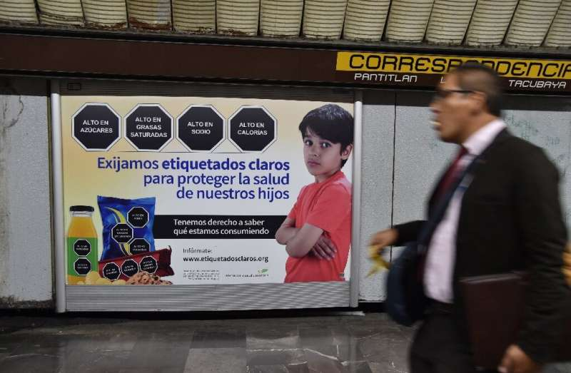 """""""We demand clear labeling to protect the health of our children,"""" reads the sign in the Mexico City subway, which show"""