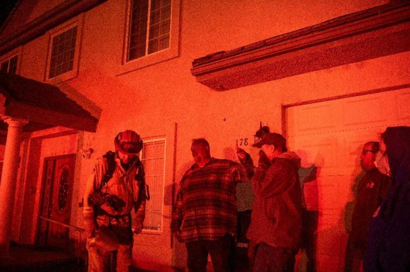 Residents speak with a firefighter in the glow of the the Hillside Fire in the North Park neighborhood of San Bernardino, Califo