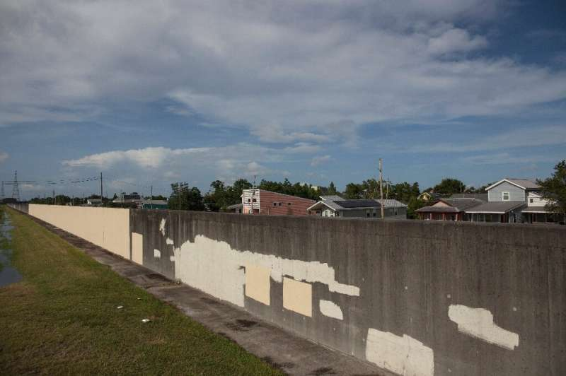 Roof tops from a neighborhood in New Orelans' 9th ward are seen behind a wall that was breached in 2005 during Hurricane Katrina