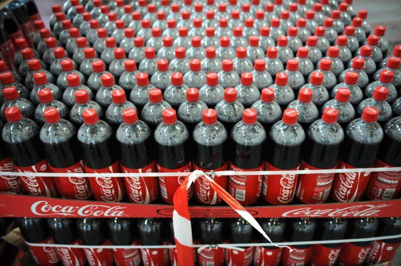 Shares of Coca-Cola rose early Tuesday after the company lifted some of its profit targets