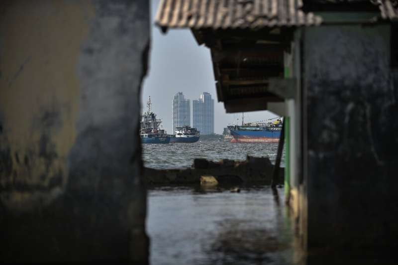 Ships are seen from an abandoned submerged mosque's walls in northern Jakarta