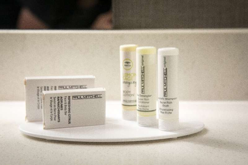 Small plastic bottles of shampoo, conditioner and body lotion sit in a bathroom in a room at a SpringHill Suites, a hotel operat
