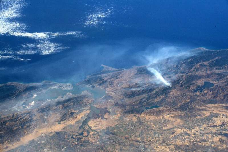 Smoke rises from the Kincade Fire (R) in Sonoma County, northern California, in this undated handout image provided by NASA and