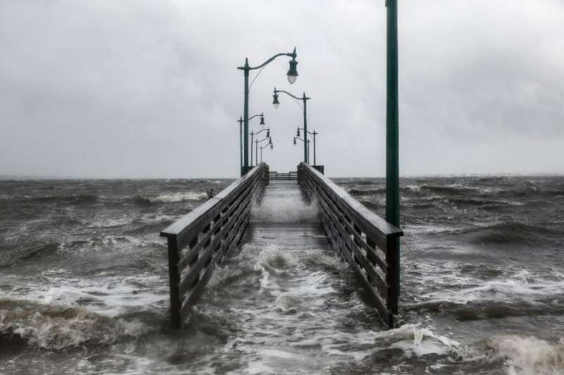 Strong gusts of wind and bands of heavy rain cover a walkway in Jensen Beach, Florida on September 3