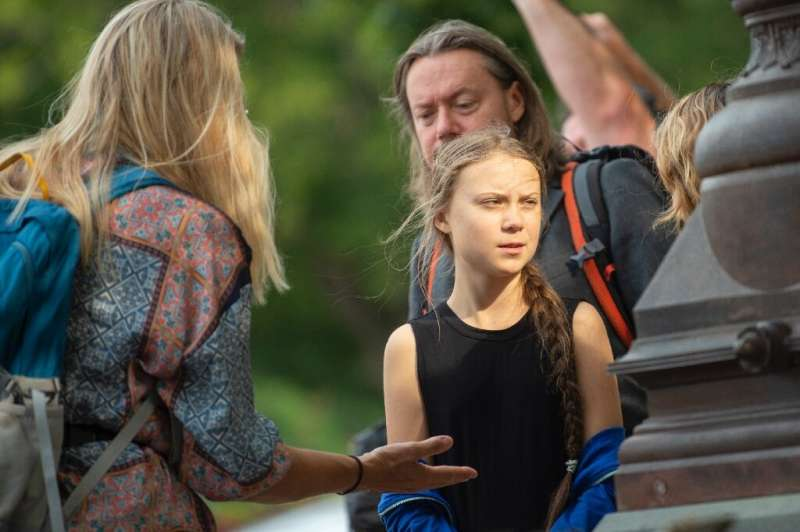 Swedish environmental activist Greta Thunberg (C) talks with members of her close entourage as she takes part in a media event o