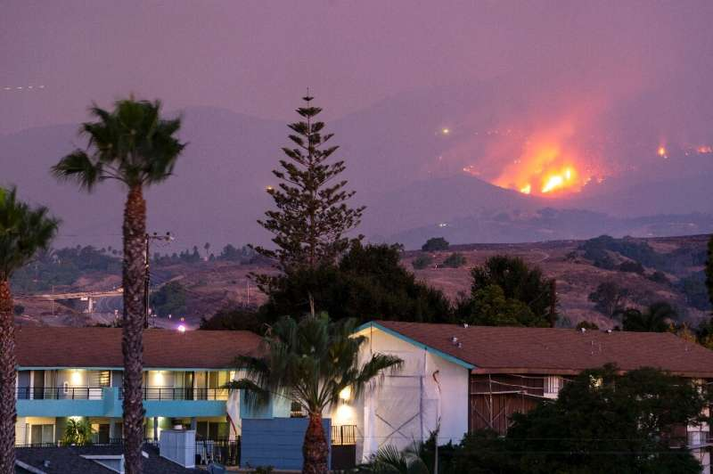 The Cave fire burns a hillside above houses in Santa Barbara, California on November 26, 2019ing homes.