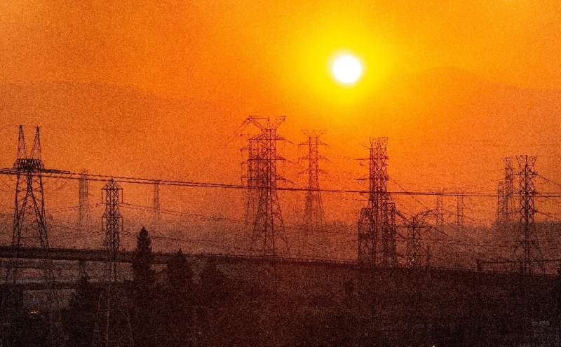 The sun rises over power lines along a smokey horizon during the Saddleridge Fire in Newhall, California on October 11, 2019