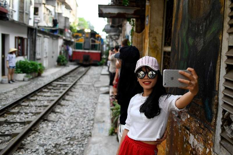 This photograph taken on June 8, 2019 shows a woman taking a selfie as a train passes in Hanoi's popular train street—the selfie