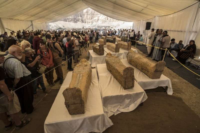 Tourists observe sarcophagi displayed in front of Hatshepsut Temple in Egypt's Valley of the Kings in Luxor