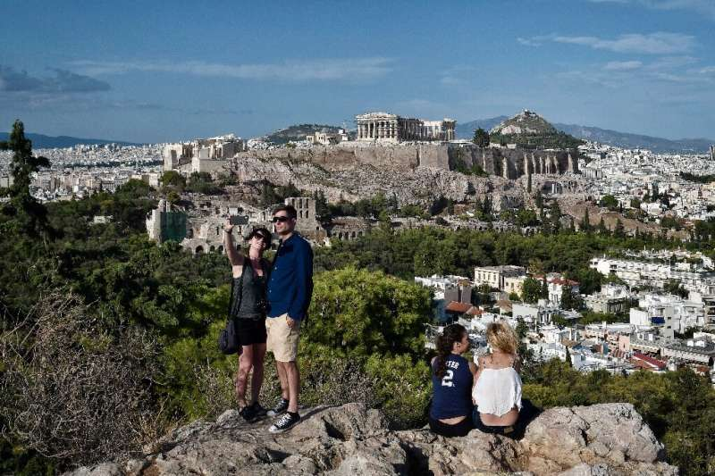 Tourists take a selfie with the Acropolis in the background