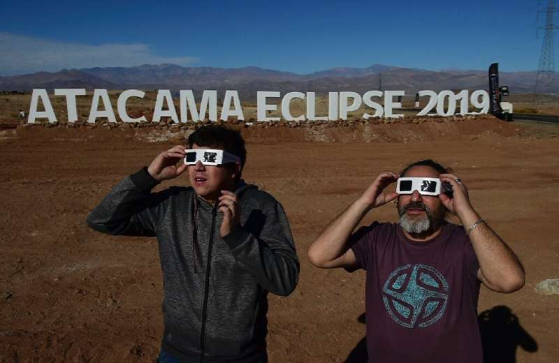 Tourists try special glasses at the entrance of an astronomical camp where thousands will observe the July 2 total solar eclipse