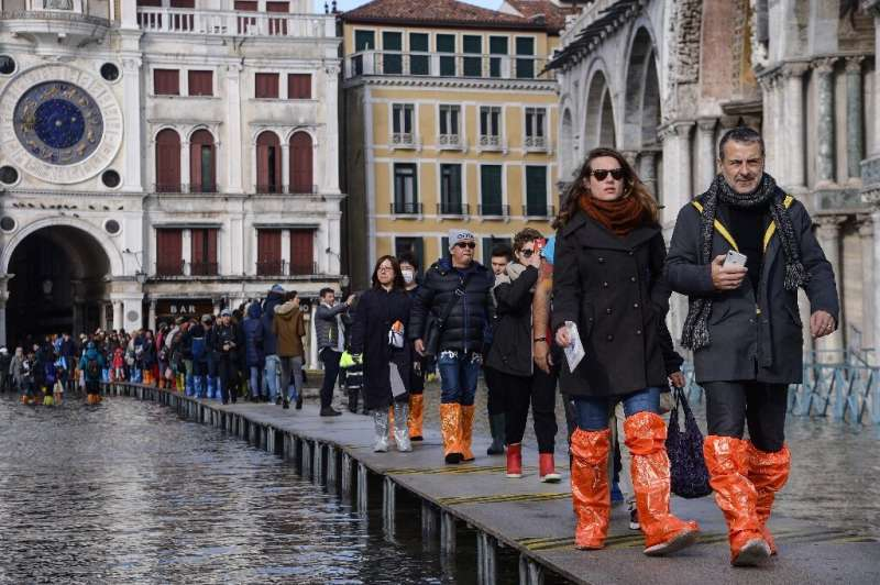 Undeterred by the crisis, tourists have been larking around in the flooded St Mark's Square