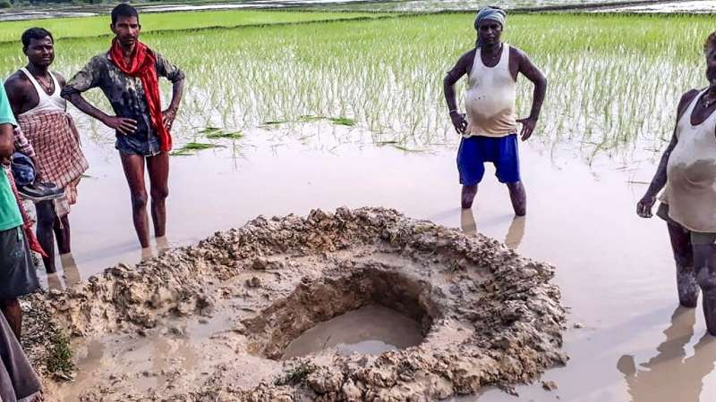 Villagers and farmers gather around the crater formed when a suspected meteorite crashed into a rice paddy in Madhubani district