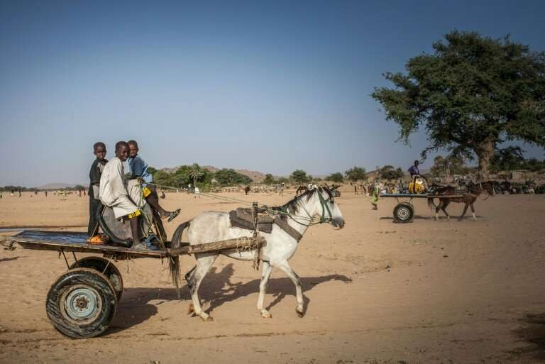 Water vendors in the arid Ouaddai district of Chad travel back and forth between meagre supplies and needy folk in town