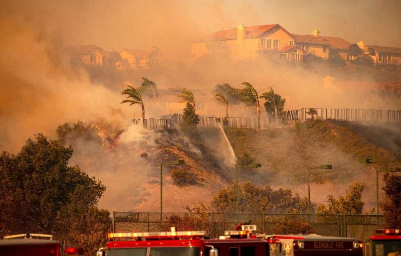 Wind whips through the area as firefighters fight impending flames during the Saddleridge fire in the Porter Ranch section of Lo