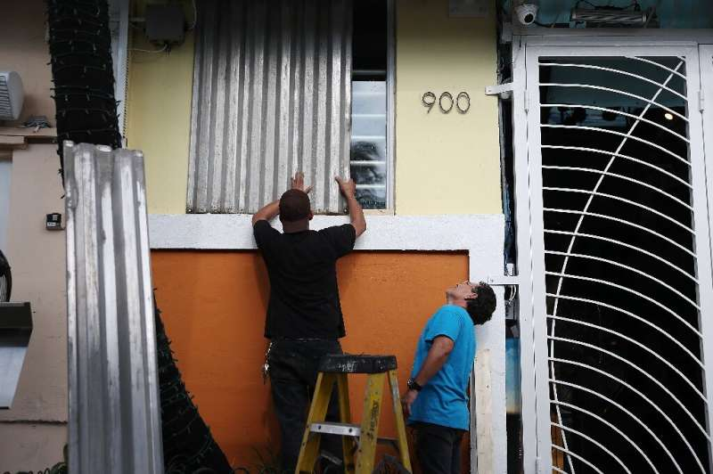 Workers place shutters over a window as they prepare for the possible arrival of Hurricane Dorian in Miami Beach, Florida