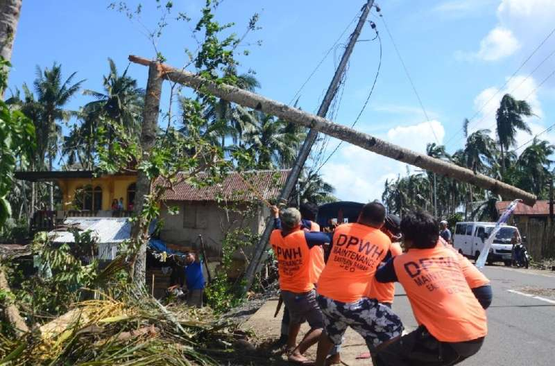 Workers pull a fallen electric pylon damaged at the height of Typhoon Phanfone in Salcedo town, Eastern Samar province of the Ph