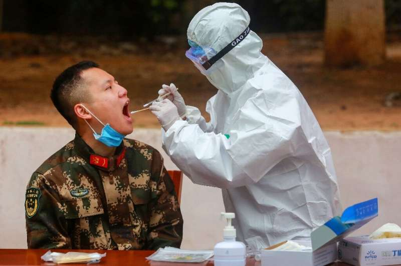 A medical worker takes a swab for testing from a Chinese paramilitary police officer in Shenzhen, Guangdong province