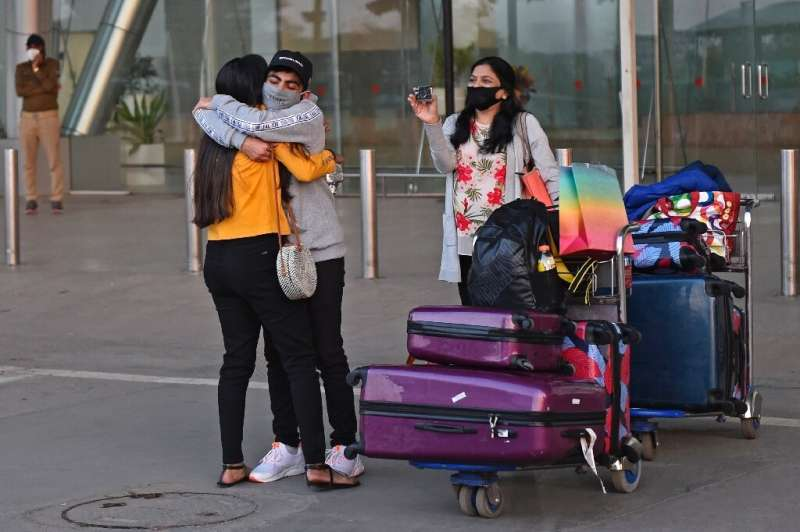 A passenger arriving from Britain is hugged by a relative at Sardar Vallabhbhai Patel International Airport in Ahmedabad before