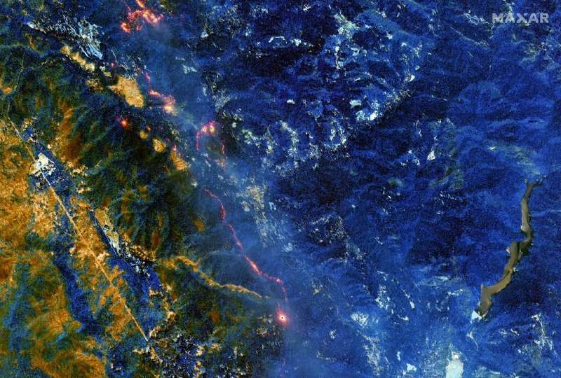 A satellite image shows burned vegetation in a rust/orange color while healthy vegetation appears in blue, and active fires from