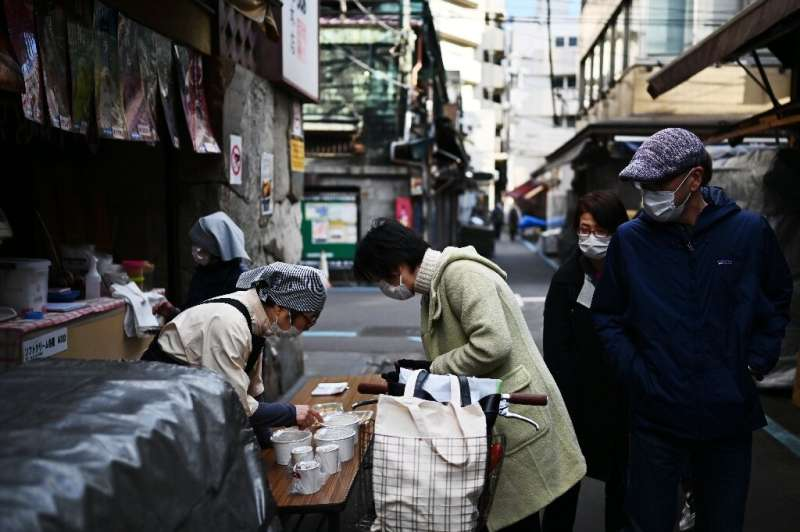 A woman in a face mask buys food from a vendor in Tokyo