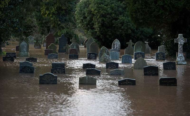 Flood water surrounds tomb stones at a graveyard in Tenbury Wells, after the River Teme burst its banks in western England