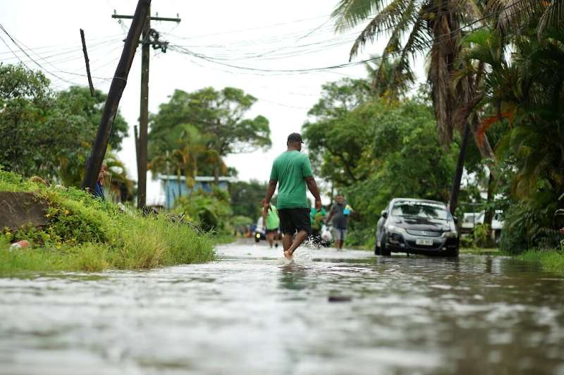 Residents wade through flooded streets in Fiji's capital city of Suva on December 16, 2020, ahead of super cyclone Yasa