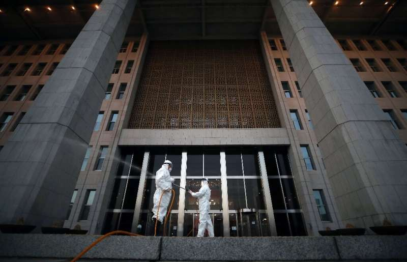 Workers spray disinfectant outside the National Assembly in Seoul, as the number of coronavirus infections continued to rise