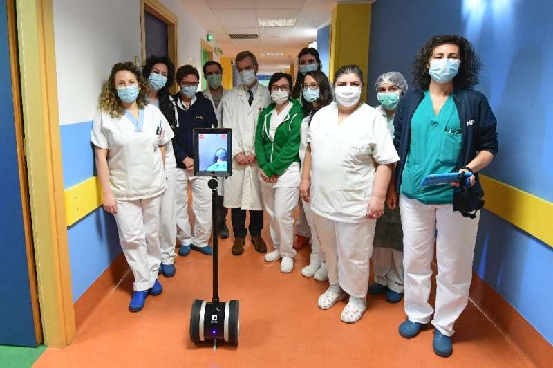 Medical staff in Varese, northern Italy, with Ivo the robot who helps them treat seriously ill coronavirus patients and reduce t