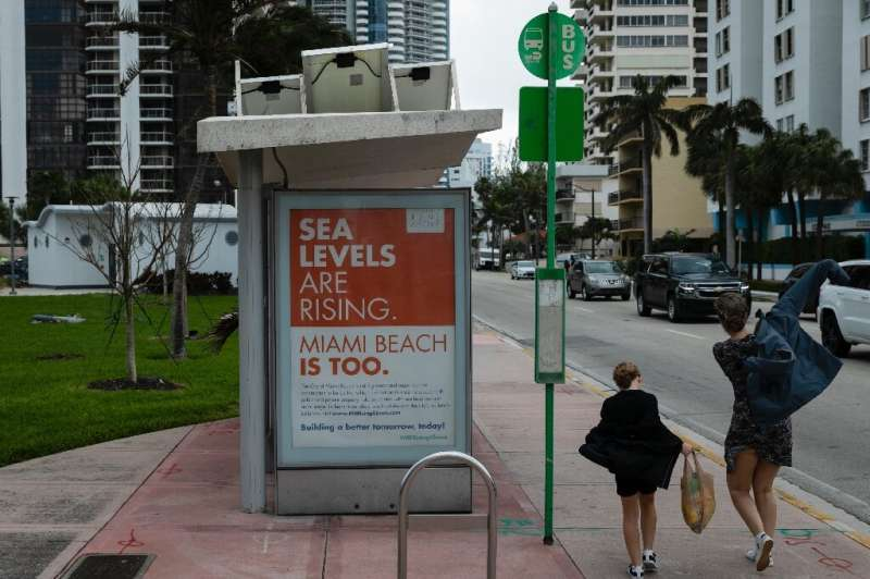 People walk past a billboard in Miami Beach discussing sea level rise: dozens of trucks have started dumping hundreds of thousan