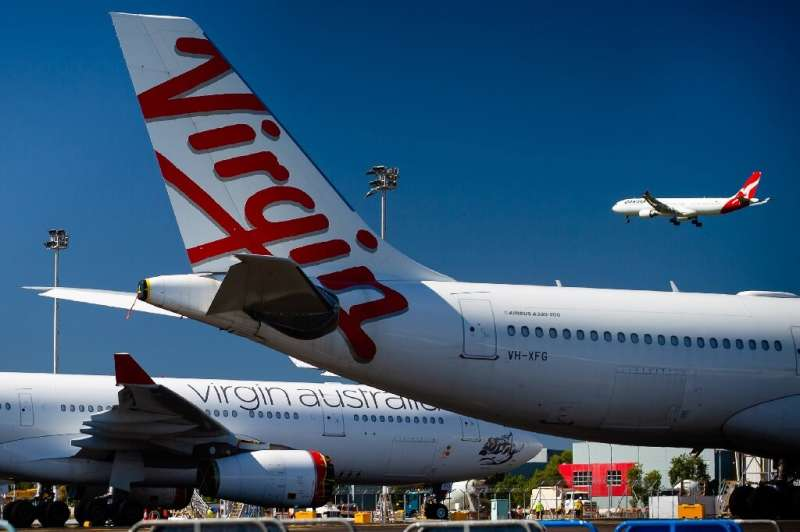 Virgin Australia aircraft are parked on the tarmac at Brisbane International airport while a plane from Qantas, the only other A