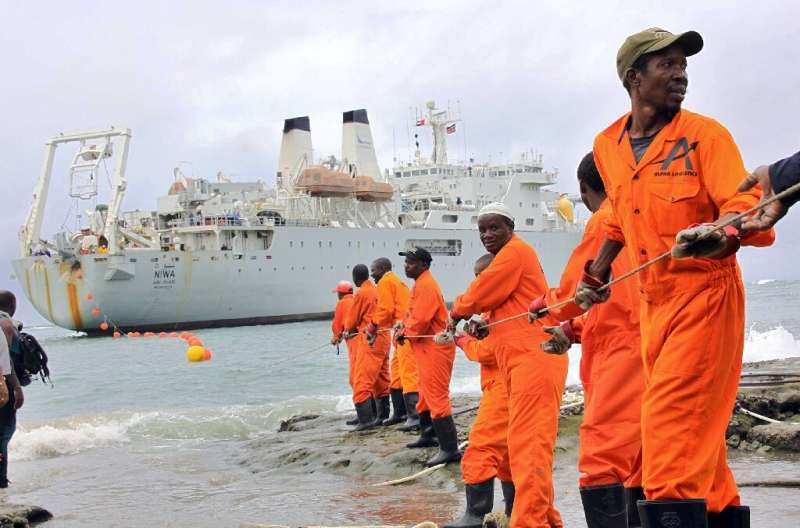 Workers at the Kenyan port of Mombasa haul ashore a fibre optic cable in June 2009 as part of a scheme to boost internet connect