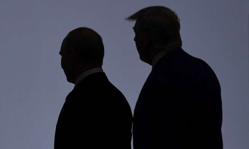 US President Donald Trump (R) walks in 2019 with President Vladimir Putin of Russia, which has been blamed for a massive cyberat
