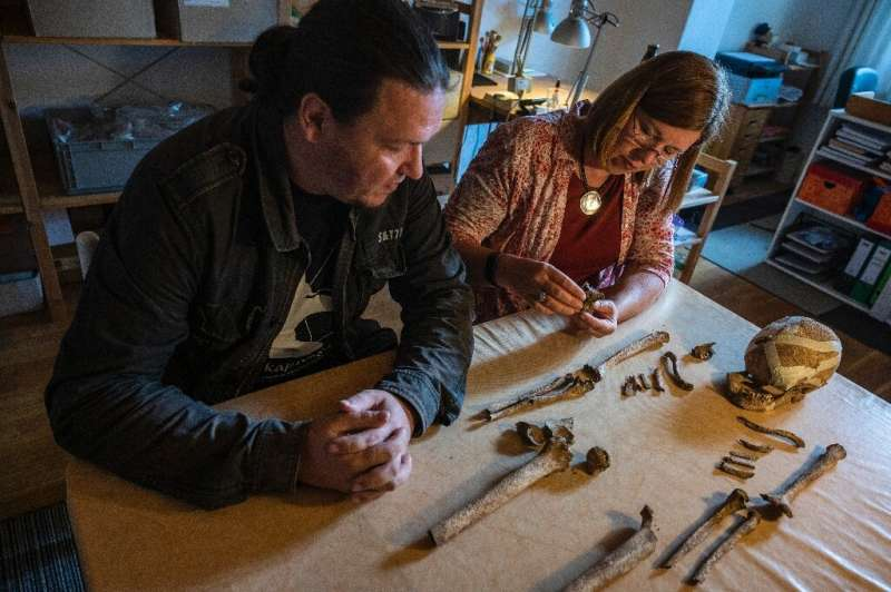 Archaeologist Philipp Roskoschinski (L) and anthropologist Bettina Jungklaus look at the skeletal remains of the so-called &quot