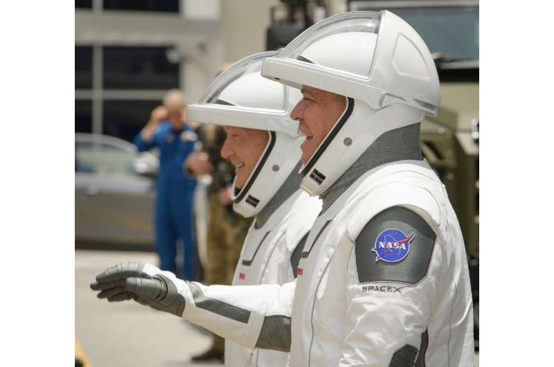 NASA astronauts Douglas Hurley, left, and Robert Behnken, wearing SpaceX spacesuits, are seen as they depart the Neil A. Armstro