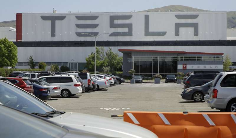 Tesla parking lot nearly full, indicating factory is running
