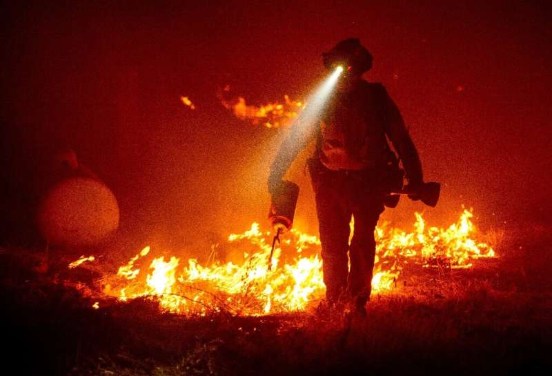 Firefighters cut defensive lines and light backfires to protect structures behind a CalFire fire station during the Bear fire