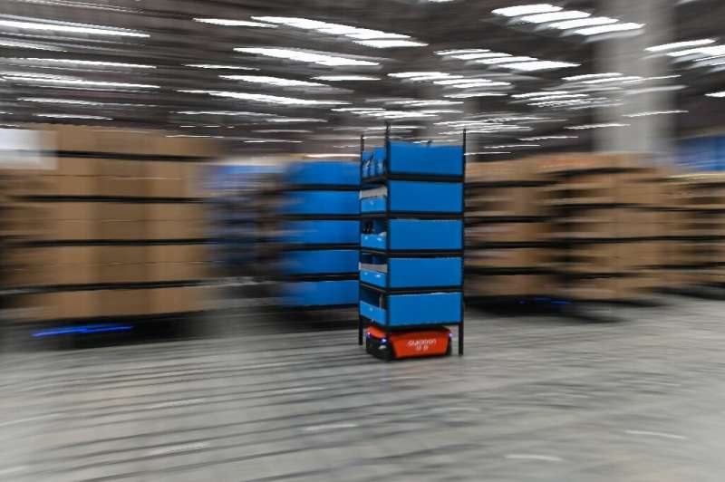A blue robot moves between aisles at the Wuxi warehouse of Cainiao Smart Logistics Network, an affiliate of e-commerce giant Ali