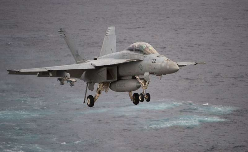 A Boeing EA-18G Growler lands on the deck of the USS George H.W. Bush aircraft carrier in the Atlantic ocean on October 25, 2017